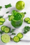 Ny grön smoothie med grönkål, gurka, limefrukt, äpple, persilja på det vita brädet Arkivbild