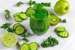 Ny grön smoothie med grönkål, gurka, limefrukt, äpple, persilja på det vita brädet Arkivfoton