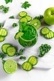 Ny grön smoothie med grönkål, gurka, limefrukt, äpple, persilja på det vita brädet Arkivbilder