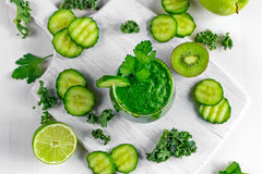 Ny grön smoothie med grönkål, gurka, limefrukt, äpple, persilja på det vita brädet Royaltyfri Fotografi