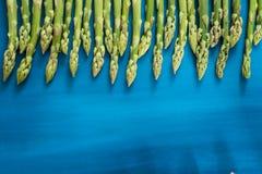 Ny grön sparrisforsmodell, på en bästa sikt för blå träbakgrund arkivbilder