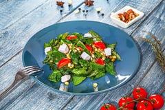 Ny grön strikt vegetariansallad som tjänas som i blå platta på blå träbakgrund med ingridents spenat kikärt, ost sund mat royaltyfri foto
