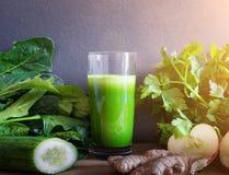 Ny grön sund detoxfruktsaft i exponeringsglas som omges av grönsaker och frukter Royaltyfri Foto