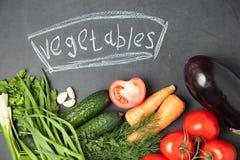 Ny grönsak på grafitbräde med en inskrift Top beskådar lök, vitlök, persilja, gurka, aubergine, tomat och dill royaltyfri foto
