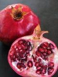 Ny granatäpplefrukt och den klippta halvan med ljusa vin-röda arils, står ut på en svart bakgrund och inviterar att äta arkivfoton