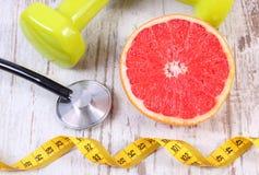 Ny grapefrukt, cm, stetoskop och hantlar, sunda livsstilar Arkivfoto