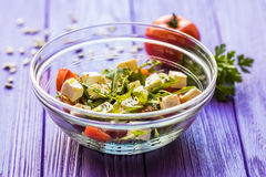 Ny grekisk sallad i en bunke nära tomate, bästa sikt på trätabellen Royaltyfri Bild