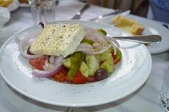 Ny grekisk sallad på en vit platta Royaltyfri Bild