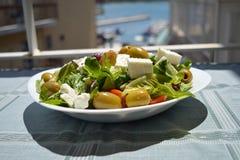 Ny grekisk sallad på en vit platta i solen Arkivfoto
