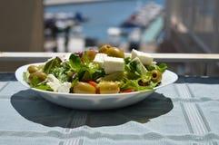 Ny grekisk sallad på en vit platta i solen Royaltyfri Bild