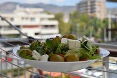 Ny grekisk sallad på en vit platta i solen Royaltyfri Fotografi