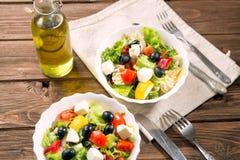 Ny grekisk sallad som göras av den körsbärsröda tomaten, feta, oliv, löken och kryddor Caesar sallad i en glass bunke på trätabel Royaltyfri Bild