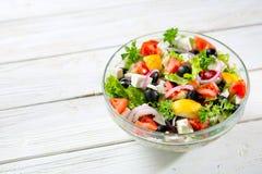 Ny grekisk sallad som göras av den körsbärsröda tomaten, feta, oliv, löken och kryddor Caesar sallad i en glass bunke på trätabel Fotografering för Bildbyråer