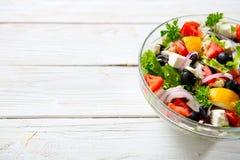 Ny grekisk sallad som göras av den körsbärsröda tomaten, feta, oliv, löken och kryddor Caesar sallad i en glass bunke på trätabel Arkivfoton