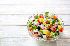 Ny grekisk sallad som göras av den körsbärsröda tomaten, feta, oliv, löken och kryddor Caesar sallad i en glass bunke på trätabel Royaltyfri Fotografi