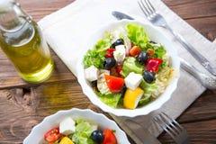 Ny grekisk sallad som göras av den körsbärsröda tomaten, feta, oliv, löken och kryddor Caesar sallad i en glass bunke på trätabel Royaltyfri Foto