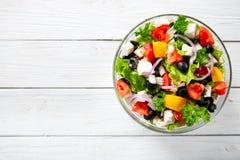 Ny grekisk sallad som göras av den körsbärsröda tomaten, feta, oliv, löken och kryddor Caesar sallad i en glass bunke på trätabel Royaltyfria Bilder