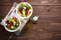 Ny grekisk sallad som göras av den körsbärsröda tomaten, feta, oliv, löken och kryddor Caesar sallad i en glass bunke på trätabel Arkivbilder