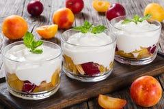 Ny grekisk yoghurt med körsbärsröda plommoner i glass koppar Arkivbilder