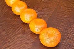 Ny grupp av mandarines i en träbakgrund arkivfoto