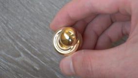 Ny guld- rastlös människaorbiter som rotera i handen av en ung man på grå bakgrund stock video