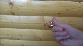 Ny guld- rastlös människaorbiter som rotera i handen av en ung man på träbakgrund arkivfilmer