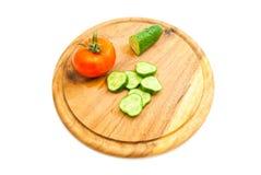Ny gurka och röd tomat på skärbräda Arkivbilder