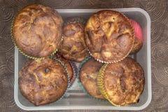 Ny hand - gjorda muffin i genomskinlig ask på mörk träbakgrund Arkivfoto