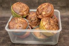 Ny hand - gjorda muffin i genomskinlig ask på mörk träbakgrund Arkivfoton