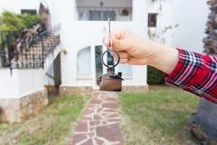 Ny hem, hus, egenskap och hyresgäst - fastighetsmäklare som räcker en hustangent royaltyfri bild