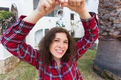 Ny hem, hus, egenskap och hyresgäst - ung rolig kvinna som framme rymmer som är nyckel- av hennes nya hem, når att ha köpt fastig royaltyfri bild
