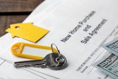 Ny hem- köp- och försäljningsöverenskommelse Tangent med keyringen och mellanrum och pengar på en brun trätabell Begrepp av att k royaltyfria foton