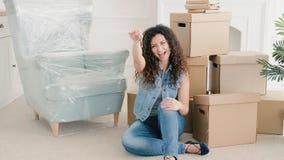 Ny hem- lycklig ung dam som visar upp lägenhettangenter