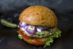Ny hemlagad hamburgare med kryddig sås, cornichons och örter över mörk metallbakgrund fotografering för bildbyråer