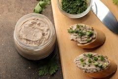 Ny hemlagad pate för feg lever med gräsplaner på bröd på en mörk bakgrund En smörgås royaltyfri fotografi