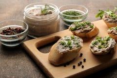 Ny hemlagad pate för feg lever med gräsplaner på bröd på en mörk bakgrund En smörgås royaltyfri foto