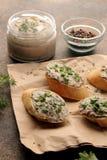 Ny hemlagad pate för feg lever med gräsplaner på bröd på en mörk bakgrund En smörgås arkivbild