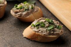 Ny hemlagad pate för feg lever med gräsplaner på bröd på en mörk bakgrund En smörgås Närbild royaltyfri foto