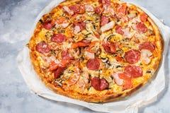 Ny hemlagad pizza med peperoni-, skinka-, ost- och tomatsås på lantlig konkret bakgrund Royaltyfria Bilder