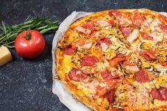 Ny hemlagad pizza med peperoni-, skinka-, ost- och tomatsås på lantlig stenbakgrund Arkivfoto