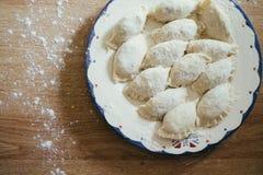 Ny hemlagad ravioli, klimpar eller pelmeni som täckas i mjöl på en trätabell Rått okokt Royaltyfri Foto