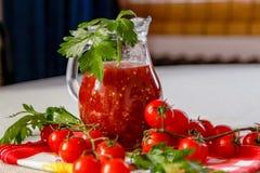 Ny hemlagad tomatfruktsaft i en exponeringsglaskrus arkivbild