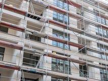 Ny hyreshus som täckas med materialet till byggnadsställning Arkivfoto