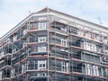 Ny hyreshus som täckas med materialet till byggnadsställning Arkivbilder