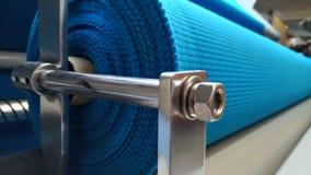 Ny industriell blåttrulle, blå bakgrund Begrepp: material tyg, tillverkning, plaggfabrik, nya prövkopior av tyger fotografering för bildbyråer