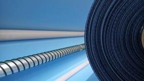 Ny industriell blåttrulle, blå bakgrund Begrepp: material tyg, tillverkning, plaggfabrik, nya prövkopior av tyger arkivbild