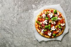Ny italiensk pizza med champinjoner, skinka, tomater, ost på på täckningpapper, konkret bakgrund för grå färger kopiera avstånd arkivfoto