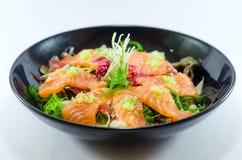Ny japansk lax i svart maträtt på vit bakgrund Arkivbilder