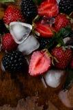 Ny jordgubbar, björnbär och mintkaramellsidor och is på träbakgrunden Tappning close upp Royaltyfri Fotografi