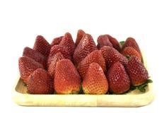 Ny jordgubbe i ett woddenmagasin i isolerad bakgrund Royaltyfri Bild